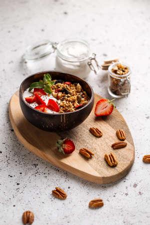 Granola yogurt with strawberries and chia seeds on the wooden board Фото со стока