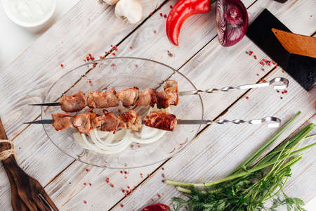 Top view on caucasian grilled meat skewers shashlyq on the light wooden table