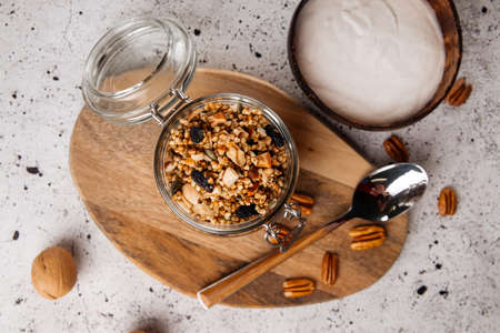 Top view on healthy breakfast yogurt in wooden bowl with granola on the light background