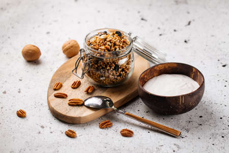 Healthy breakfast yogurt in wooden bowl with granola on the light background
