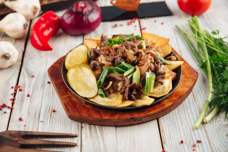Fried potatoes with beef and green onions in cast iron pan on the light wooden table Фото со стока