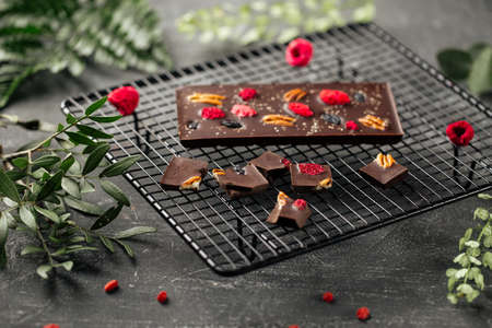 Handmade chocolate bar with pecan nuts and dried berries