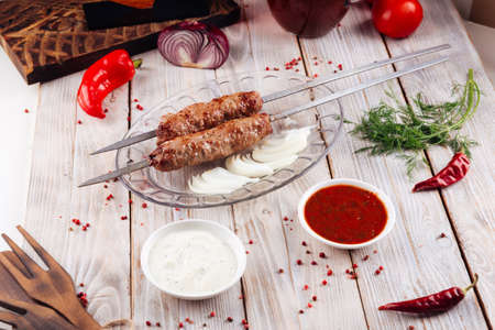 Caucasian grilled meat skewers lula kebab on the light wooden table