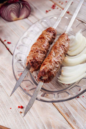 Closeup on caucasian grilled meat skewers lula kebab on the light wooden table