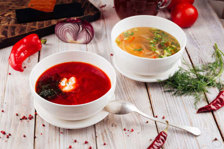 Side view on two soups borsch and vegetable on the light wooden table