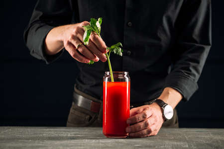Man making bloody mary cocktail with celery Stock Photo