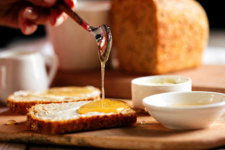 Side view on spreading bread slice with honey