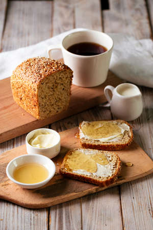 Whole grain bread slices with butter and honey Фото со стока