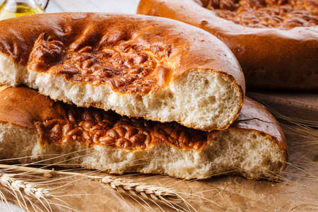 Closeup on broken fresh baked onion flat bread Фото со стока