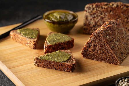 Sliced diet grain bread spread with pesto sauce Фото со стока