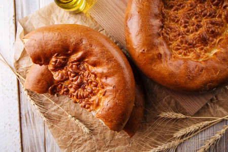 Top view on broken fresh baked onion flat bread