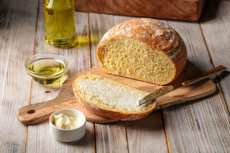 Cut loaf of olive oil bread spread with butter Фото со стока