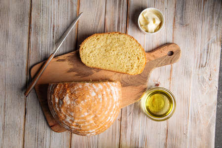 Cut loaf of olive oil bread on the wooden table Фото со стока