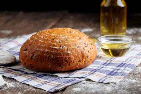 Side view on loaf of rustic bread with olive oil