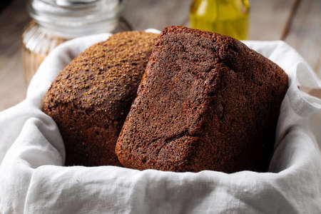 Two loafs of rye bread in a basket with napkin Фото со стока