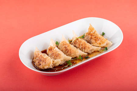 Japanese gedza dumplings with soy sauce on pink