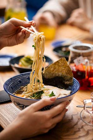 Eating shio ramen noodle soup with chopsticks