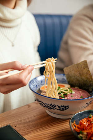 Eating shoyu ramen noodle soup with chopsticks