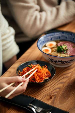 Eating asian marinated carrot and shoyu ramen