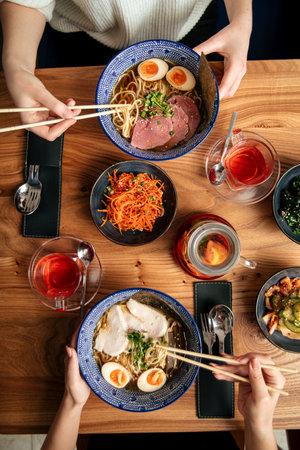 Two people eat japanes ramen noodle soups Фото со стока