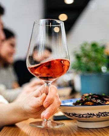 Hand holding a wine glass of aperole cocktail Фото со стока