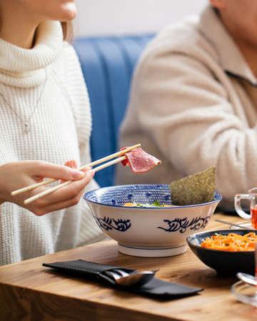 Eating japanese ramen noodle soup with chopsticks Фото со стока
