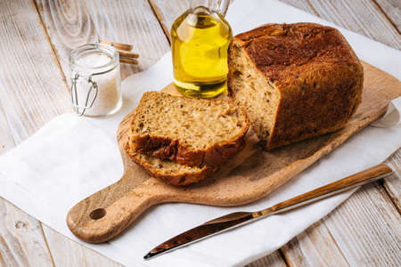 Sliced black bread on wooden board with olive oil