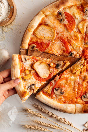 Taking a slice of fresh baked chicken pizza
