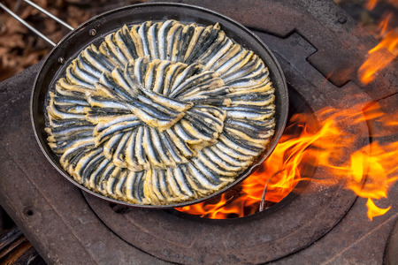 anchovies in frying pan, on old stove