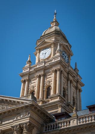 Limestone edwardian clock tower on blue sky background