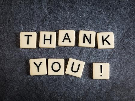 Letter tiles on black slate background spelling Thank You! 免版税图像
