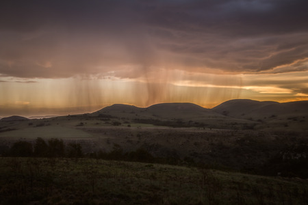 Rain falling on a distant mountain with orange sunset