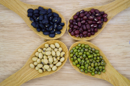 black gram: Mung bean, Soy bean, Black gram and Red bean in wooden spoon on cutting board Stock Photo