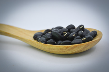 black gram: Black gram in wooden spoon on Isolated background Stock Photo