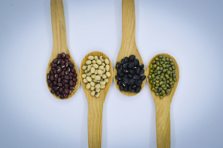 black gram: Mung bean, Soy bean, Black gram and Red bean in wooden spoon on Isolated background Stock Photo