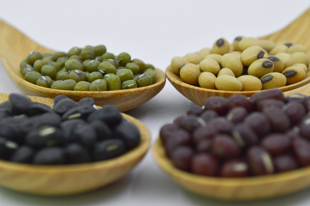 red gram: Mung bean, Soy bean, Black gram and Red bean in wooden spoon on Isolated background Stock Photo