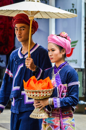 Chiang Rai, Thailand - July 7, 2017 : Candle Festival Parades are paraded around Chiang Rai town.  In Thailand associates with Buddhist agenda called Buddhist Lent. Girl hold an offering and bathrobe