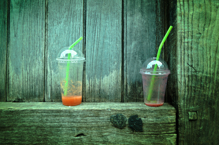 Garbage, juices glass is put on the wooden door Stock Photo