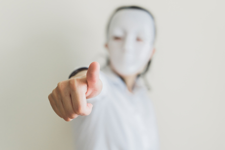 inexpressive: Asian woman wearing white mask thumbs up
