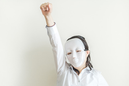inexpressive: Asian woman wearing white mask striking victory pose