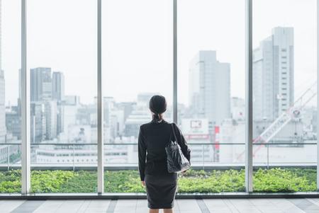 ビジネスの女性を見て大きなウィンドウから大都市 写真素材