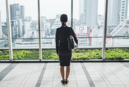 Business woman sees a large city from big window pane
