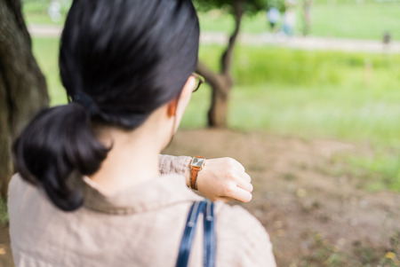 office time: Asian woman looking at her watch Stock Photo