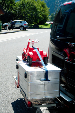 strapped: Baby rider transport on a metal box with a car