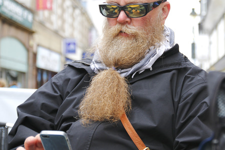 man with beard along a write email on his phone and there is a reflection in his glasses Stock Photo