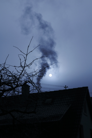 particulate: Smoke from chimney with Moon in fog in the dark evening Stock Photo