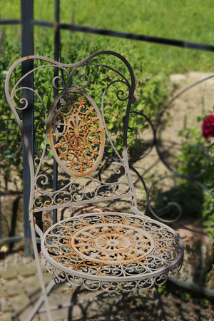 Old-fashioned rusty, more romantically, chair from metal, with playful ornaments