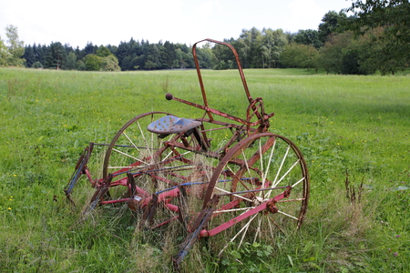 Age, rusty tractor, combine harvester on a meadow, a field 版權商用圖片