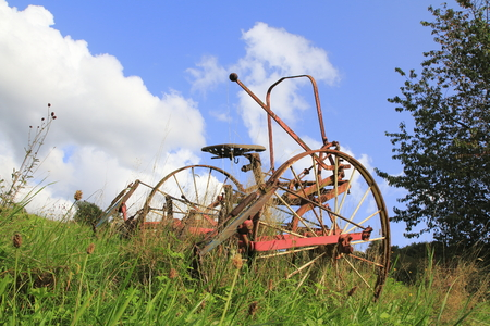 Age, rusty tractor, combine harvester on a meadow, a field Stock Photo
