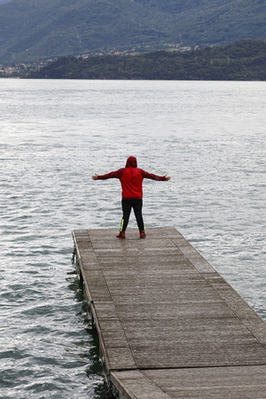 Man stands on a jetty, dressed in sweatpants and hoodie, on Lake Como with outstretched arms and looks to Colico Stock Photo